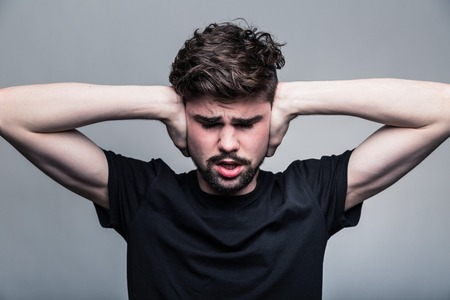 I need silence. Frustrated young man in shirt and tie covering ears with hands and keeping eyes closed while standing against grey background photo