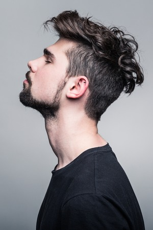 Studio portrait of young handsome man with fashion hairstyle
