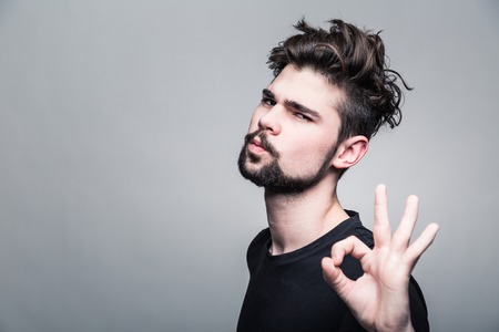 Young man in  black T-shirt shows gesture okey Foto de archivo