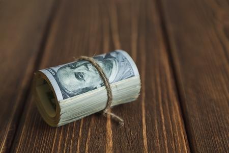 onehundred: Stacks of one hundred dollars banknotes on wooden desk Stock Photo