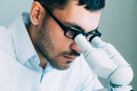Closeup of young male doctor viewing through microscope Stock Photo