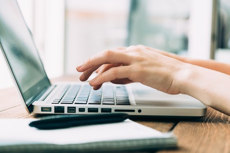 Woman working with laptop placed on the wooden desk Banque d'images