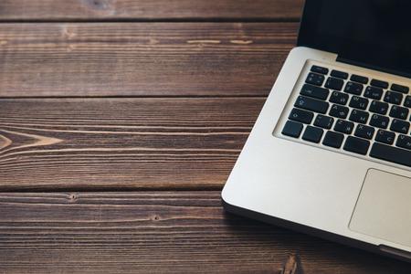 Laptop keyboard on the brown wooden desk