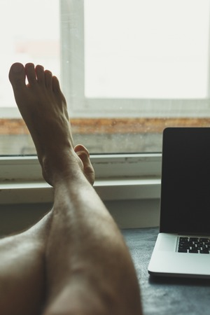 work took: Man took a break from work and put his feet on the table