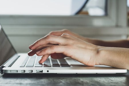 using the computer: Mujer que trabaja con la computadora portátil colocada sobre el escritorio negro