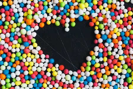 emptiness: Colorful Sugar Balls ,in the middle candys - heart of emptiness  on dark grunge metal background, top view.