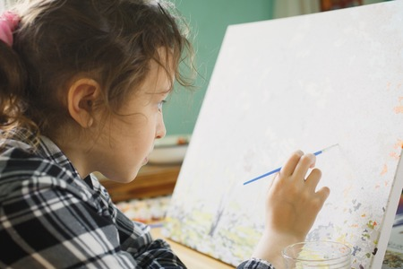 eight year old: eight year old girl in a plaid shirt with enthusiasm that paints with a brush on canvas