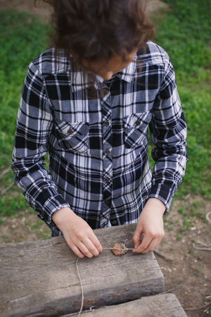 eight year old: eight year old girl in a plaid shirt plays one on the street with a rope and stone in the summer