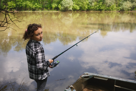 eight year old: eight year old girl in a plaid shirt catches fish in the river summer in the village Stock Photo