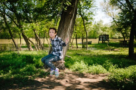 8 year old girl: 8 year old girl in plaid shirt rides a rope swing on a river in a Sunny summer day