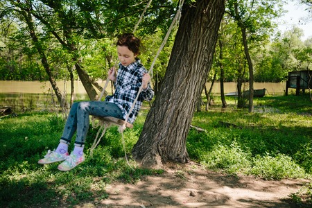 8 year old: 8 year old girl in plaid shirt rides a rope swing on a river in a Sunny summer day