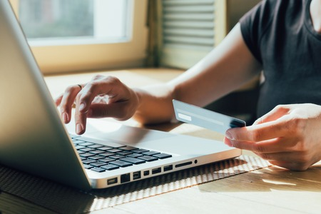 chica hace una compra en Internet en el ordenador con tarjeta de crédito Foto de archivo