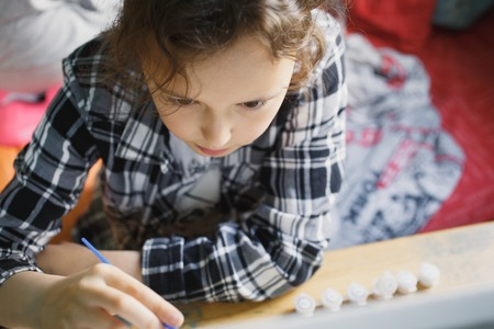 eight year old: eight year old girl in a plaid shirt with enthusiasm that paints with a brush Stock Photo
