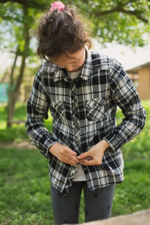 eight year old: eight year old girl buttoning a plaid shirt on a summer day Stock Photo