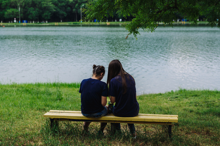 jule: ARMAVIR, RUSSIA - JULE 02, 2016: Young women sitting on a bench by the lake and take pictures of themselves Editorial