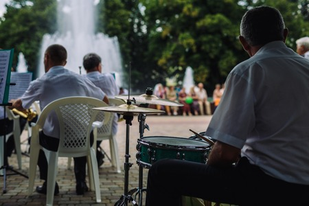 jule: ARMAVIR, RUSSIA - JULE 02, 2016: Men play musical instruments in the orchestra in the park on a summer day