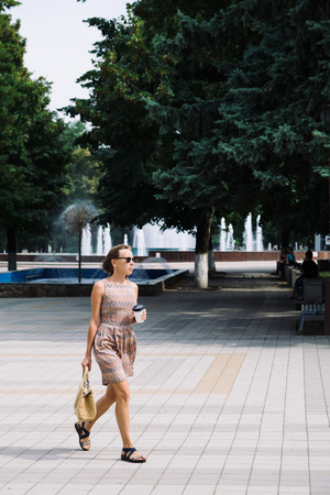 sandal tree: Portrait of young woman in dress and sunglasses walking against of fountains in park with coffee to go Stock Photo