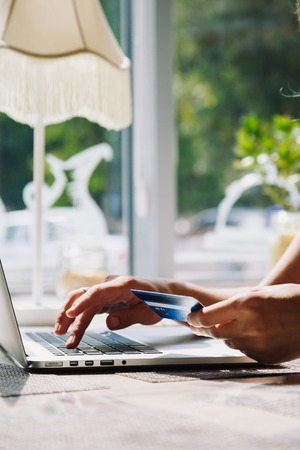 incognito: Unrecognizable woman doing online shopping with credit card using laptop in cafe Stock Photo