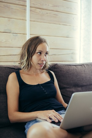 legs crossed: Portrait of attractive woman with short hair in black top using laptop while sitting on sofa with legs crossed and looking away with smile Stock Photo