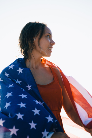 low perspective: Low perspective portrait of young smiling woman wrapped in american flag and looking away Stock Photo