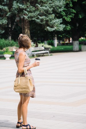 Portrait of young woman in dress and sunglasses walking against of fountains in park with coffee to go Stock Photo