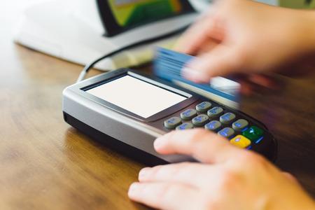 swipe: Close up of hand swipe credit card on card-reader machine