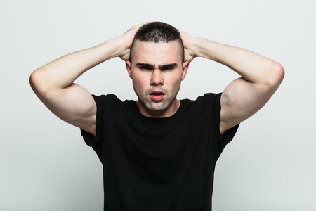 wrath: Front view of angry model man posing in studio with hands on head. Isolate. Stock Photo