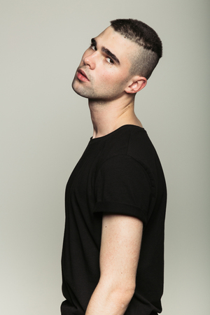 Studio shoot of young man wearing black t-shirt turned away and looking at camera. Side view. Stock Photo