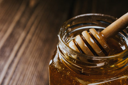 Macro crop view of glass honey jar with honey stick inside appearing slowly.