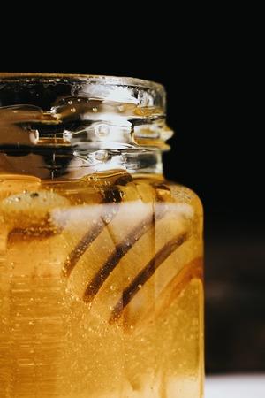 despacio: Macro crop view of glass honey jar with honey stick inside appearing slowly.