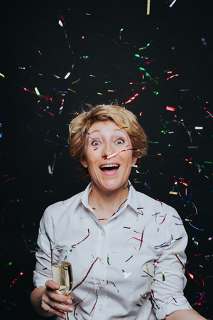 Excited middle aged woman with glass of champagne laughing in flying colorful confetti isolated on black. Banque d'images