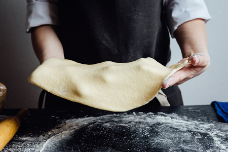 Hands of cook working with rolled shortcrust dough