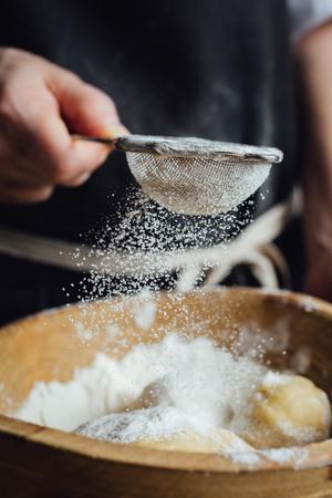 Persona agrega harina para pasteles por el colador. foto de estudio vertical. Foto de archivo