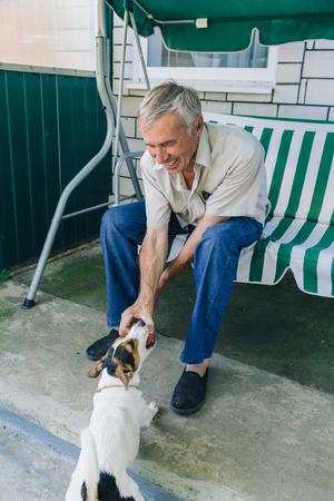Retrato de hombre senior feliz sentado en la silla de jardín y jugando con su perro Foto de archivo - 74860485