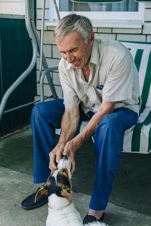 Retrato de homem sênior feliz sentado na cadeira de jardim e brincando com seu cachorro Foto de archivo - 74860484