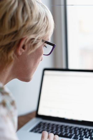 median age: Back view of female in glasses sitting and working on laptop on blurred background. Stock Photo