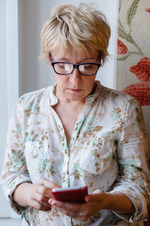 median age: Front view of mature woman in glasses standing and using device.