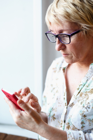 median age: Mature confident female in glasses looking at screen of smartphone.