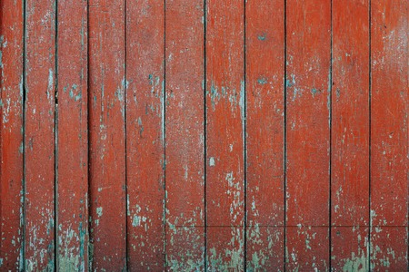 Aged peeling wooden surface painted with red paint