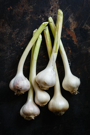 Bundle of garlic bulbs on black dish