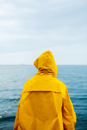 Back view of girl in yellow raincoat standing on stone pier of waterfront with ocean on background. Stock Photo