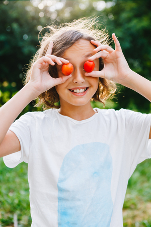 Charming girl holding plums covering eyes and smiling on background of summer garden. Stock Photo