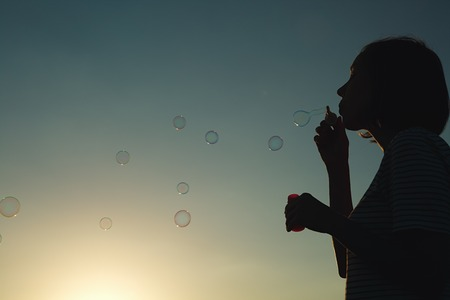 Girl inflates soap bubbles at sunset. Rear view. Banco de Imagens