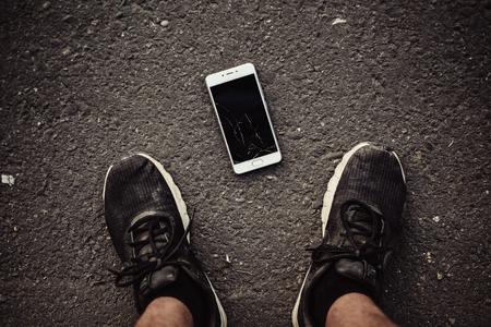 Benen en een smartphone met een gebroken scherm op een donkere achtergrond. Het uitzicht vanaf de top.