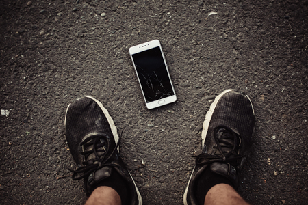 Legs and a smartphone with a broken screen on a dark background. The view from the top. Banque d'images