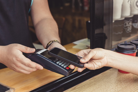 Person paying pay through smartphone using NFC technology in outdoor cafe Stock Photo