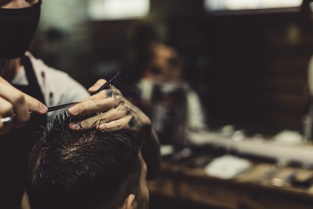 Anonymous stylish barber with tattoos cutting hair of male client in chair.