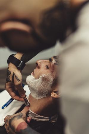 Crop stylish applying foam on customers cheeks for shaving while working in barbershop.