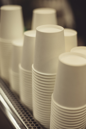 Close-up white stacked paper cups for hot beverages.