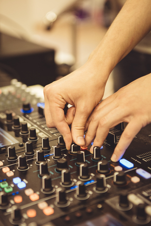 audio mixer: Close-up hands of soundman working with audio mixing board.